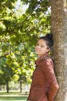Side view of attractive brunette woman leaning against a tree