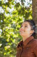 Side view of cheerful young woman leaning against a tree