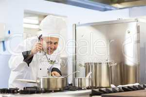 Smiling head chef tasting food from ladle