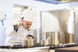 Focused head chef tasting food from ladle