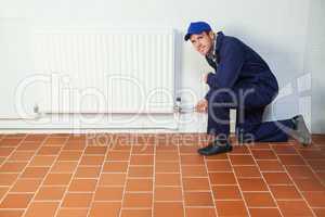 Handyman in blue boiler suit repairing a radiator smiling at cam