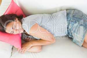 Attractive young woman sleeping on her white couch