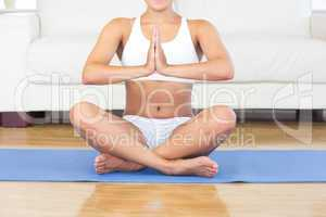 Mid section of young woman sitting in lotus position on an exerc