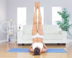 Sporty cute woman relaxing in yoga pose on blue exercise mat