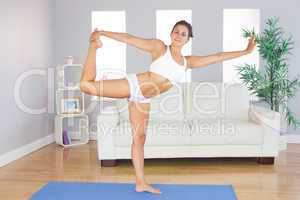Portrait of young slim woman stretching her body with yoga exerc