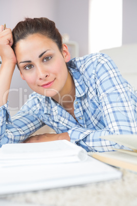 Portrait of calm young student doing assignments while lying on