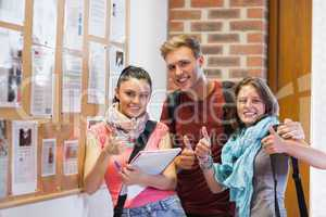Three smiling students standing next to notice board showing thu