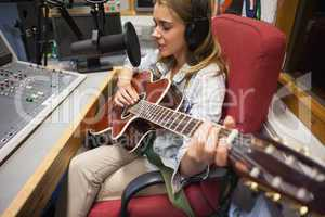 Focused pretty singer recording and playing guitar