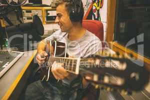 Smiling handsome singer recording and playing guitar