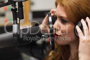 Focused beautiful singer recording a song
