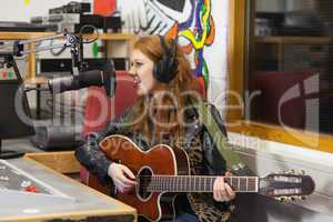 Happy beautiful singer recording and playing guitar