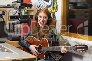 Smiling beautiful singer recording and playing guitar