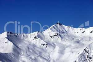 off-piste snowy slope and blue clear sky