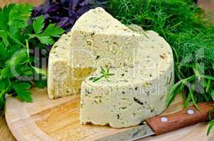 cheese round homemade with herbs and knife on board