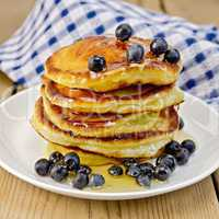 flapjacks with blueberries and honey on the board