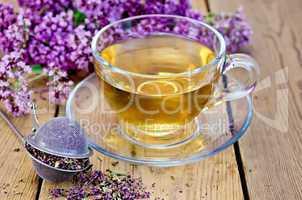 herbal tea of oregano with strainer in a glass cup