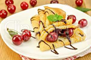 pancakes with cherry and chocolate syrup on the board