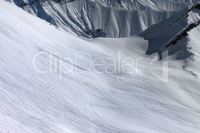view on snowy off piste slope with trace from ski, snowboards an