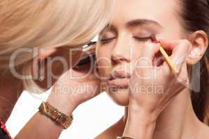 beauty stylist applying make-up to a young model
