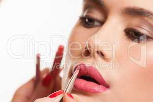 young woman having lip gloss applied