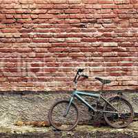 Old rusty vintage bicycle leaning against a brick wall