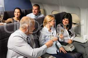 airplane cabin businesspeople toasting champagne