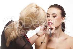 beauty stylist applying lipstick to a model