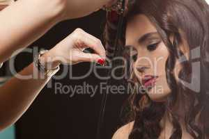 model having her hair curled by a stylist
