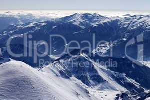 snowy mountains and off-piste slope in morning haze