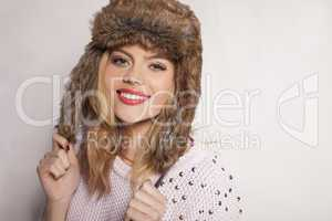 beautiful happy young woman in a furry winter hat