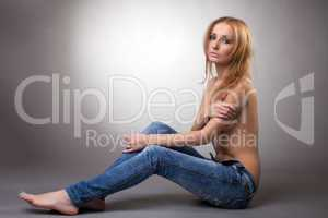 Image of slim topless woman posing in jeans