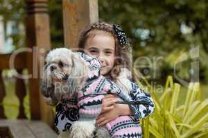 Portrait of adorable little girl hugging pet