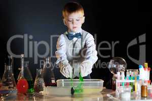 Cute schoolboy watching reaction of reagents