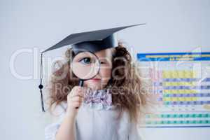 Focus on eye of little girl looking through loupe