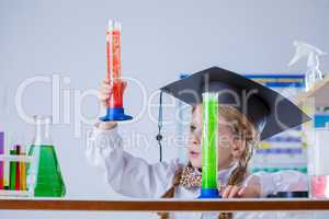 Interested schoolgirl considering colorful flasks