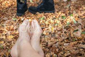 shoes and bare feet in autumn leaves