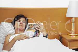 woman is lying in bed reading