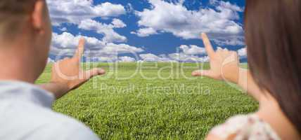 Couple Framing Hands Around Space in Grass Field