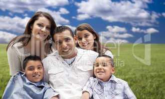 hispanic family portrait sitting in grass field