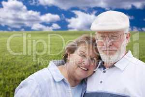 loving senior couple standing in grass field