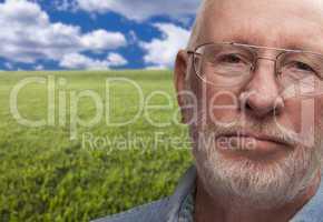 Melancholy Senior Man with Grass Field Behind