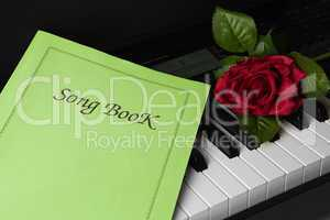 piano keys, song book,and rose flower