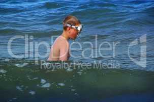 Junge mit Taucherbrille im Meer