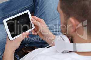 Junger Mann hört Musik auf seinem Tablet Computer