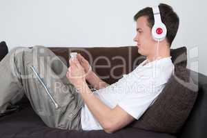 Junger Mann hört Musik auf dem Sofa