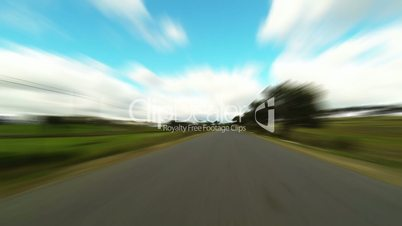 fast driving car on the road in green fields, blurred timelapse