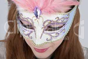 Beautiful teenage girl wearing carnival mask with pink feathers
