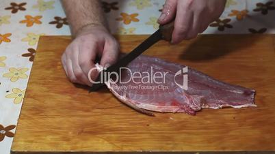 Fisherman hands with knife making fillet