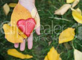 hand holding red heart and autumn leafs