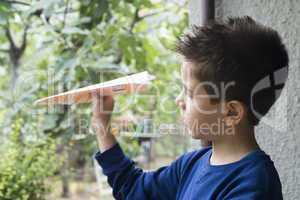 kid throws paper plane